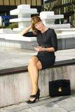 Jeune femme s'asseyant sur le banc et parlant au téléphone portable photos stock