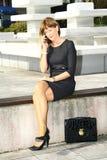 Jeune femme s'asseyant sur le banc et parlant au téléphone portable photographie stock libre de droits