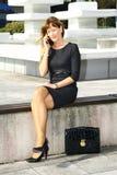 Jeune femme s'asseyant sur le banc et parlant au téléphone portable image stock