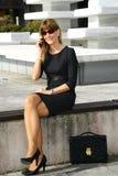 Jeune femme s'asseyant sur le banc et parlant au téléphone portable photo libre de droits