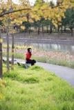 Jeune femme s'asseyant sur le banc Marguerite, liberté photographie stock libre de droits