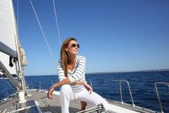 Jeune femme s'asseyant sur le bateau à voile Images stock