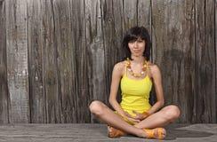 Jeune femme s'asseyant sur le bureau en bois Images libres de droits