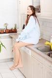 Jeune femme s'asseyant sur le compteur de cuisine photographie stock libre de droits