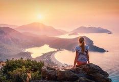 Jeune femme s'asseyant sur le dessus de la roche et regardant le seasho Photographie stock libre de droits