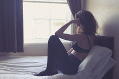 Jeune femme s'asseyant sur le lit pendant le matin Image libre de droits
