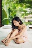 Jeune femme s'asseyant sur le lit touchant son pied blessé Photo stock