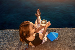 Jeune femme s'asseyant sur le pilier au lever de soleil Photographie stock libre de droits