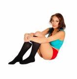Jeune femme s'asseyant sur le plancher Photographie stock