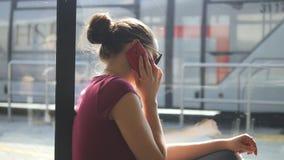 Jeune femme s'asseyant sur le plancher au salon de attente d'aéroport et parlant du téléphone Fille parlant sur le téléphone port clips vidéos