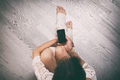 Jeune femme s'asseyant sur le plancher avec le smartphone, vue supérieure photo stock