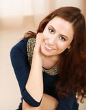 Jeune femme s'asseyant sur le plancher et le sourire Photo stock