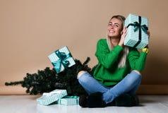 Jeune femme s'asseyant sur le plancher près de l'arbre de Noël de sapin et rêvant du présent, de l'avenir, des cadeaux et d'atten photos stock