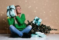 Jeune femme s'asseyant sur le plancher près de l'arbre de Noël de sapin et rêvant du présent, des cadeaux et d'attendre un miracl photos stock