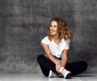 Jeune femme s'asseyant sur le plancher près du mur foncé photographie stock