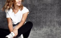 Jeune femme s'asseyant sur le plancher près du mur foncé images libres de droits