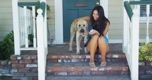 Jeune femme s'asseyant sur le porche avec son chien Image libre de droits