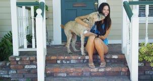 Jeune femme s'asseyant sur le porche avec son chien Images stock