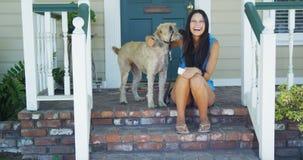 Jeune femme s'asseyant sur le porche avec son chien Photo libre de droits