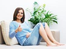 Jeune femme s'asseyant sur le pouce d'exposition de divan  Photo libre de droits