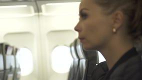 Jeune femme s'asseyant sur le siège dans la cabine d'avion avant décollage Passanger de femme se reposant dans la fin de cabine d banque de vidéos