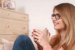 Jeune femme s'asseyant sur le sofa avec la tasse de café ou de thé dans des mains photos libres de droits