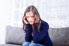 Jeune femme s'asseyant sur le sofa ayant la migraine de mal de tête Photo libre de droits