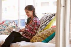 Jeune femme s'asseyant sur le sofa dans un café Image libre de droits