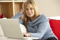 Jeune femme s'asseyant sur le sofa utilisant l'ordinateur portatif photographie stock
