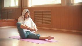 Jeune femme s'asseyant sur le tapis de yoga et s'asseyant en position de lotus banque de vidéos