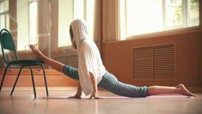 Jeune femme s'asseyant sur le tapis de yoga exécutant une fente - faisant la jambe étirant des exercices utilisant une chaise - s clips vidéos