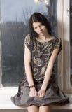 Jeune femme s'asseyant sur le windowsill Photo stock