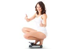 Jeune femme s'asseyant sur ses hanches sur une échelle Photographie stock