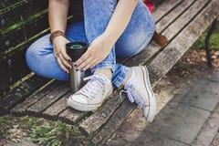 Jeune femme s'asseyant sur un banc avec une tasse de voyage de café dans des mains Image stock