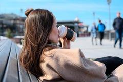 Jeune femme s'asseyant sur un banc dans un manteau et un café potable avec une tasse jetable, vue arrière du côté Photographie stock
