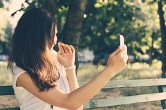 Jeune femme s'asseyant sur un banc de parc et photographiée sur un mobile Photo libre de droits