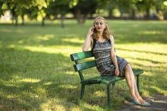 Jeune femme s'asseyant sur un banc de parc parlant à un téléphone portable Photographie stock libre de droits