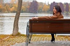 Jeune femme s'asseyant sur un banc en stationnement images stock