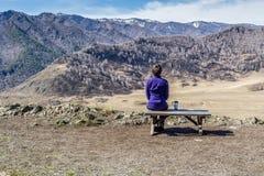 Jeune femme s'asseyant sur un banc et regardant des montagnes avec une tasse Image libre de droits