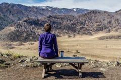 Jeune femme s'asseyant sur un banc et regardant une rivière avec une tasse de thé Images libres de droits