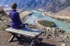 Jeune femme s'asseyant sur un banc et regardant une rivière avec une tasse de thé Photographie stock