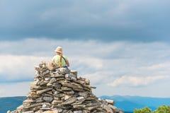 Jeune femme s'asseyant sur un dessus de montagne Photographie stock libre de droits