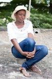 Jeune femme s'asseyant sur un morceau de brique Photos libres de droits