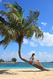 Jeune femme s'asseyant sur un palmier de dépliement Photographie stock