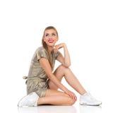Jeune femme s'asseyant sur un plancher et recherchant Photographie stock
