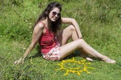 Jeune femme s'asseyant sur un pré près des fleurs jaunes dans une forme du soleil Images stock