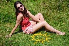 Jeune femme s'asseyant sur un pré près des fleurs jaunes dans une forme du soleil Photos libres de droits