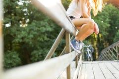 Jeune femme s'asseyant sur une balustrade de pont dans des espadrilles de jeans Photos stock