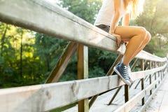 Jeune femme s'asseyant sur une balustrade de pont dans des espadrilles de jeans Photo libre de droits