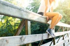 Jeune femme s'asseyant sur une balustrade de pont dans des espadrilles de jeans Photographie stock libre de droits